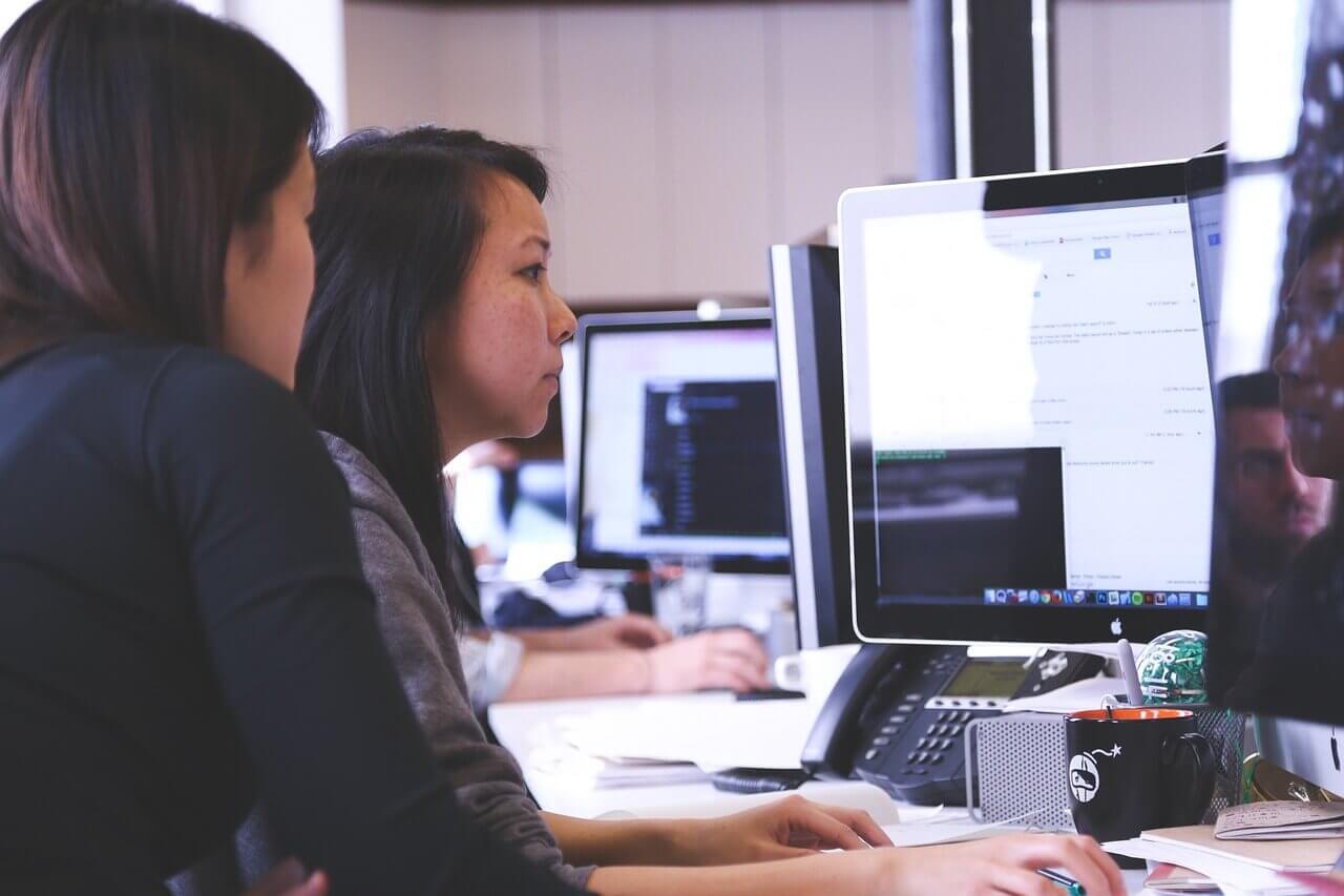 Deux collaboratrices travaillent derrière un écran