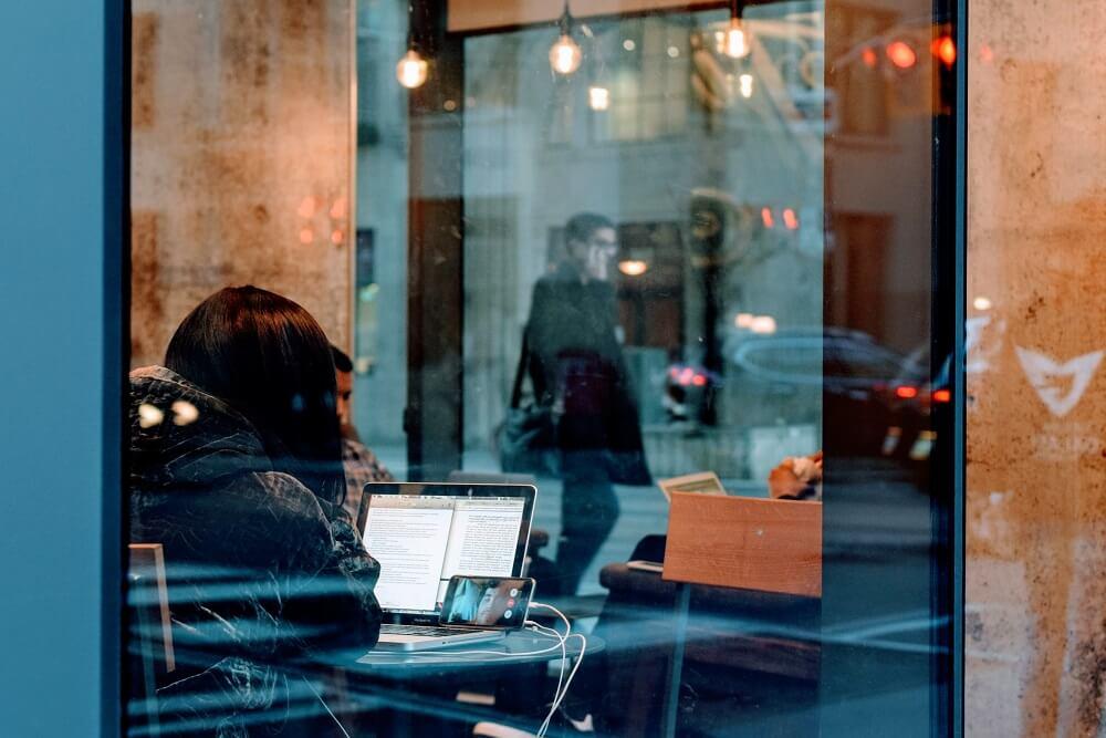 Personne travaillant au café avec un ordinateur et un smartphone