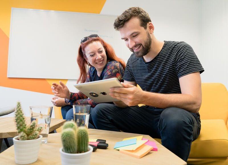 Deux collaborateurs regardent une tablette et deux castus