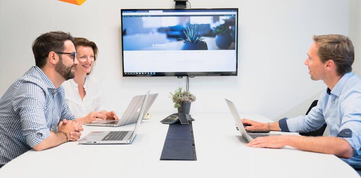 Trois collaborateurs en réunion avec un écran de télévision et trois ordinateurs